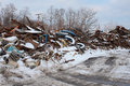 Metal scrap heap piles are shown in recycling yard in winter with coating of snow conveying hard industrial edge Stock Photography