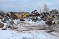Metal scrap yard piles are shown in recycling in winter with coating of snow accenting hard industrial setting Royalty Free Stock Images