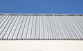 Metal sheet wall with blue sky. Royalty Free Stock Photo