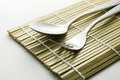 Metal spoon and fork on bamboo mat with light shadow effect Stock Image