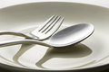 Metal spoon and fork on dish with light shadow effect Royalty Free Stock Images