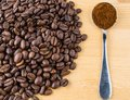 Metal spoon with ground coffee on table with coffee beans Royalty Free Stock Photo