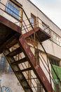 Metal staircase rising up the old building strong abandoned with painted walls in protected room with bars on windows Royalty Free Stock Photo