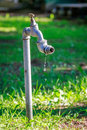 Metal tap dripping water drops unattended on the cemetery Royalty Free Stock Images