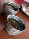 Metal tea cups two on wood table Royalty Free Stock Images