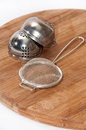 Metal tea strainer on the wooden board Royalty Free Stock Photography
