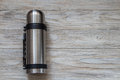 Metal thermos flask on a woden background. Top view Royalty Free Stock Photo