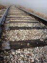Train tracks leading around a curve and off into the fog Royalty Free Stock Photo