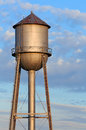 Metal water tower and morning sky an old tank in the light of the sun stands tall against a cloudy blue in americas midwest Stock Photos