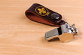 Metal whistle with leather key chain on wooden background. Royalty Free Stock Photo