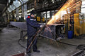Metal worker grinds weld steel sections using an angle grinder.