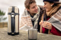 Metalic cup and thermos outdoors with couple closeup of hot beverage in a wooden table young under blanket blurred on the Royalty Free Stock Photos