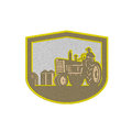 Metallic farmer driving tractor plowing farm shield retro styled illlustration of a worker a vintage field set inside crest done Royalty Free Stock Images