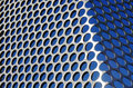 Metallic grid aluminum perforated against a blue sky under sun light Stock Photos