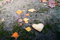 Metallic heart on stone among autumn leaves with small depth of