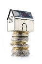 Metallic model house on a pile of coins, isolated on white Royalty Free Stock Photo
