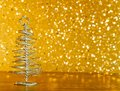 Metallic modern christmas tree on wood table on golden tint light bokeh background Royalty Free Stock Photo