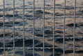 Metallic net with drops against sea background. Royalty Free Stock Photo