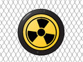 Metallic nuclear sign against a wire fence Stock Photo