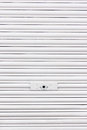 Metallic roller shutter with door lock