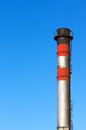 Metallic smokestack against blue sky Stock Photography