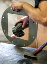 Metalworker sanding a metal component with disc sander smoothing the edges on square Royalty Free Stock Photo