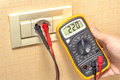 Metering socket voltage with digital multimeter Royalty Free Stock Photography