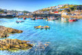 Mevagissey harbour cornwall uk blue sea and sky on a beautiful summer day in vibrant and colourful hdr boats england Royalty Free Stock Photo