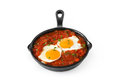 Mexican breakfast: Huevos rancheros in iron frying pan isolated Royalty Free Stock Photo