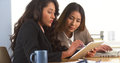Mexican businesswoman sharing findings on tablet with japanese colleague in the office Royalty Free Stock Photos