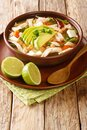 Mexican caldo tlalpeno soup  made with homemade chicken stock  a chipotle tomato base  and shredded chicken closeup on the table. Royalty Free Stock Photo