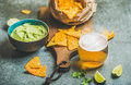 Mexican corn chips, fresh lime, guacamole sauce and wheat beer Royalty Free Stock Photo