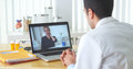 Mexican doctor video chatting with elderly patient at desk Stock Photo