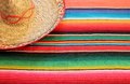 Mexican fiesta poncho rug in bright colors with sombrero traditional background copy space Royalty Free Stock Image