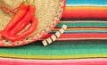 Mexican fiesta poncho rug in bright colors with sombrero traditional background copy space and chilli Royalty Free Stock Image