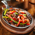 Mexican food beef fajitas and bell peppers shot close up in iron skillet Royalty Free Stock Photos