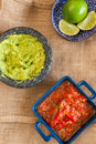 Mexican food fiesta setting on table cloth red salsa limes and guacamole Royalty Free Stock Photography