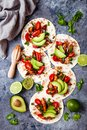 Mexican grilled chicken tacos with avocado, tomato, onion on rustic stone table. Recipe for Cinco de Mayo party.