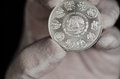 Mexican libertad silver coin hand held was shot on a black background and with a white glove Royalty Free Stock Photography