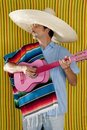 Mexican man serape poncho sombrero playing guitar Royalty Free Stock Photos