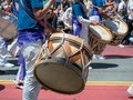 Mexican marching band beats on drums while walking down streets