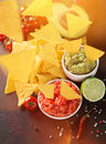 Mexican nacho chips and salsa dip on black stone background Stock Photo