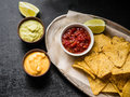 Mexican nachos chips in a wooden box with salsa sauce, cheese sauce and guacamole sauce and lime slice Royalty Free Stock Photo