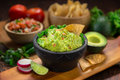 Mexican restaurant style side of Guacamole food and chips on a wood cutting board vertical shot with salsa Royalty Free Stock Photo