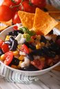 Mexican salsa with black beans and corn chips close up. Vertical Royalty Free Stock Photo