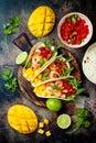 Mexican shrimp tacos with avocado, tomato, mango salsa on rustic stone table. Recipe for Cinco de Mayo party.