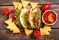 Mexican tacos with meat and nachos on a wooden table Royalty Free Stock Photo