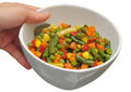 Mexican vegetable mix a hand holding a food bowl with with beans peas corn pepper carrots Stock Images