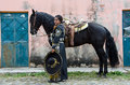 Mexican woman and black horse young in traditional outfit standing by andalusian on cobblestone street in village Royalty Free Stock Images
