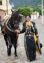 Mexican woman and black horse young in traditional outfit walking with andalusian on cobblestone street in village Royalty Free Stock Photos